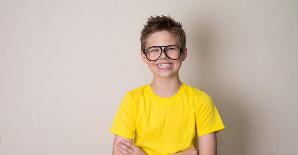 Health, education and people concept. Happy teen boy in braces and eyeglasses smiling..jpg