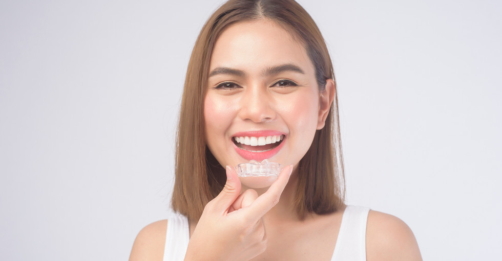 A young smiling woman holding invisalign braces over white background studio, dental healthcare and Orthodontic concept..jpg