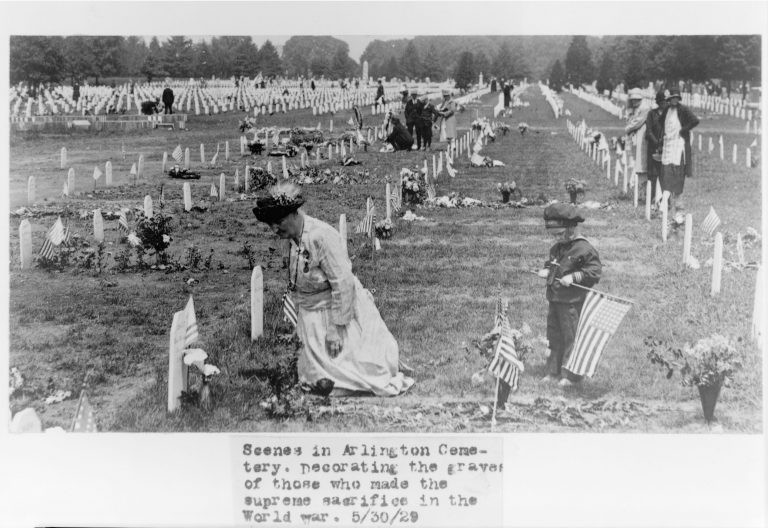 Setting in Arlington, with many graves decorated with gifts, ribbons, flags and flowers. Center-frame:  A woman dressed in white and a hat kneels above the resting place of a loved one who lost their lives while serving in the US military.