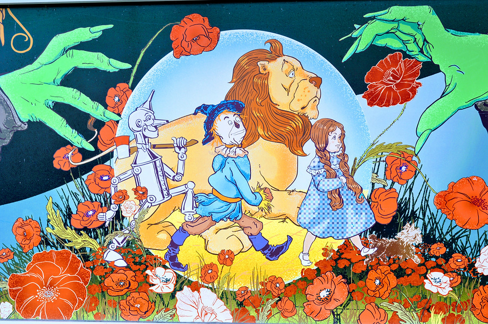 """Artwork from the exterior of the Oz Museum, Wamego Kansas. The Wizard of Oz """"Dorothy, Tin Man, The Cowardly Lion, and Toto in a poppy field."""""""