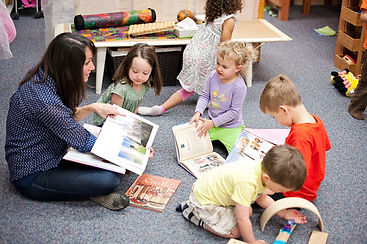 children reading with a teacher