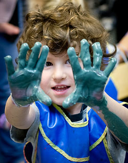 boy holding up hands covered in blue finger paint