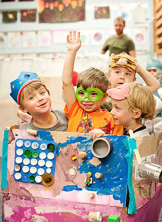 boys dressed in masks showing off their artwork