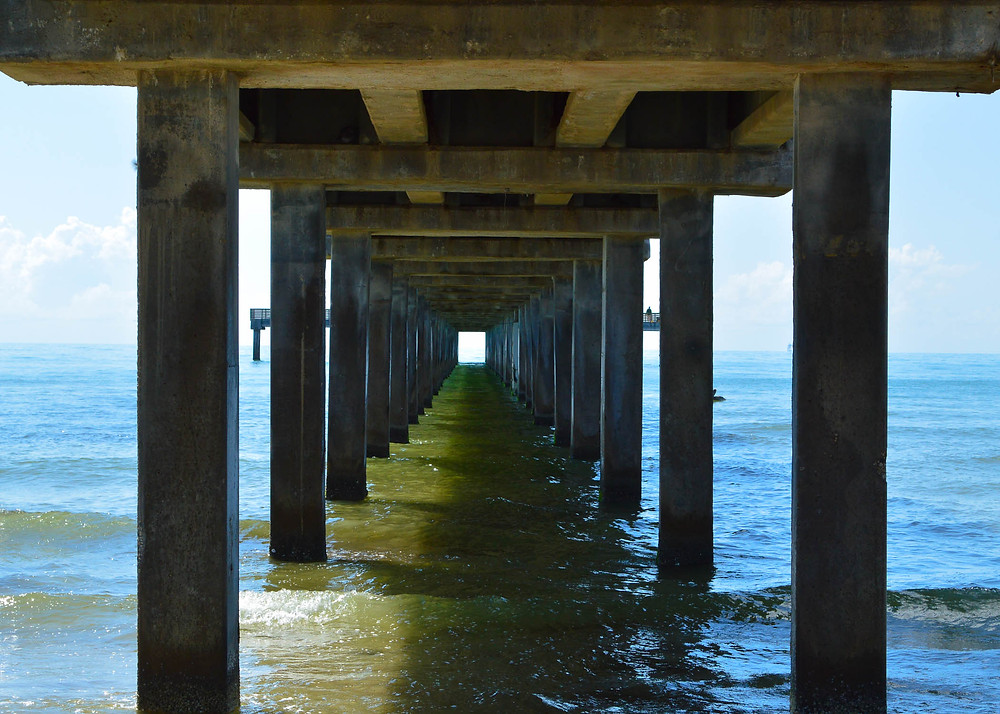 photo under a ocean pier looking out to ocean with sun shining on the water at Port Aransas Texas in the summer clear day
