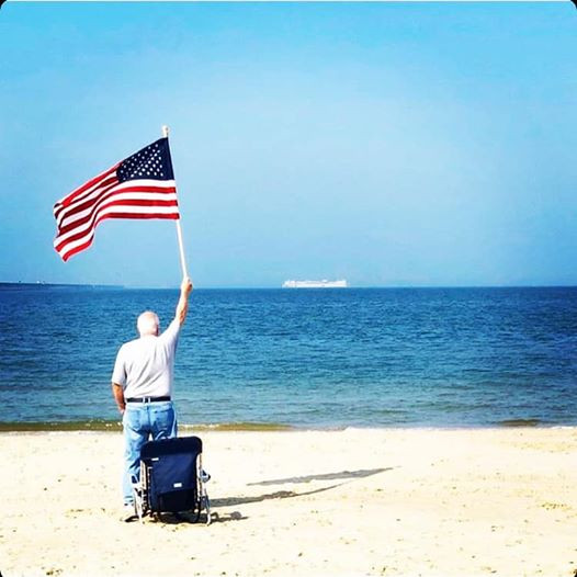 photo of elderly man standing on empty beach holding the american flag looking out to sea as the USNS Comfort hospital ship deport Norfolk, Virginia heading to NYC for covid help in the spring of 2020