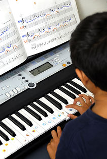 An young kid learning to play the piano.