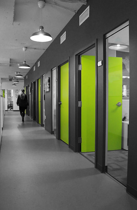 Bright green doors line the hallway of IUCN's offices. Commerical interior architecture design by bldg in Washington DC.