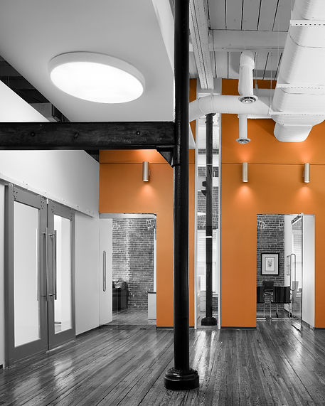 A bright orange wall and hardwood floors add warmth to the lobby of this space at 901 7th St. Designed by bldg in Washington DC. Commercial interior architecture in Washington DC.