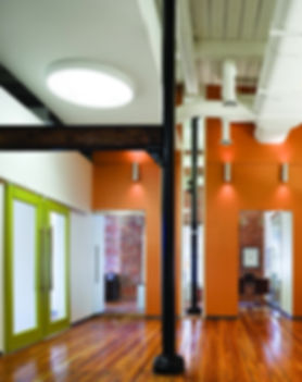 Bright orange and lime green and warm wood tones make this a unique and fun office designed by bldg in Washington DC.