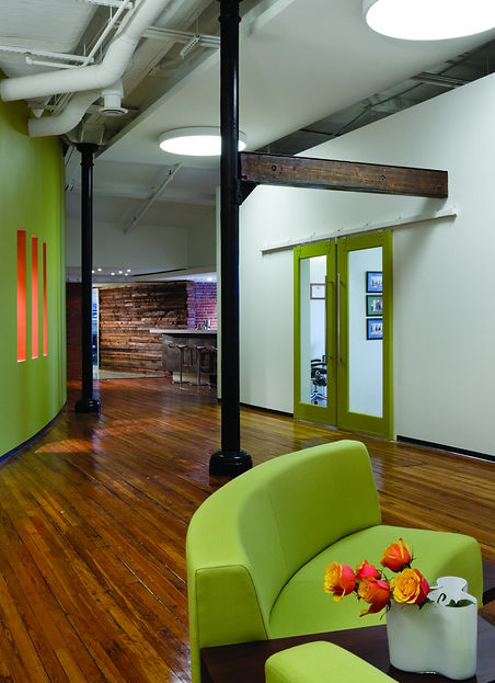 Lime green furniture makes a statement on the warm tones of the original hard wood flooring. The space was designed by bldg in Washington DC.