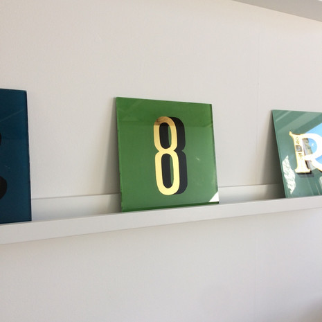 A private commission of a number 8. Painted by hand and in reverse with a bespoke green mixed by hand to make a unique - one off - piece of work. The gilding has been applied to the back of the glass using the technique of water gilding and on this piece Umberto chose 23c gold. - The number has a block shadow to it's right painted in black. - In this piece the number 8 came from a typeface designed for the American singer-song writer, John Mayer. The typeface known as 'Mayer' was designed by David A Smith of Torquay who kindly gave Umberto the typeface to use across projects that may require it.   Dimensions:  230 x 230mm  Thickness:  6mm