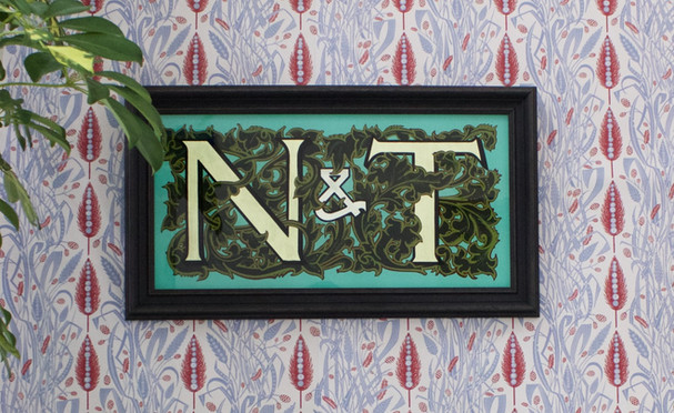 N & T  N & T commissioned as a wedding gift. This glass piece was oil gilded in reverse, a technique that gives the gold a matt appearnce. - Both letters are gilded using 18c gold and the ampersand uses 12c gold which has a white gold appearance. - The whole piece was drawn by hand prior to making and each colour has been mixed to make a truly unique bespoke piece, a nice touch for a special occasion. - The acancthus scrolling around the lettering has three colours applied, two of which are outlines and detailing to the structure of the scrolling leaves. - The frame was bespoke made by our friends Saddleworth Picture Framers. The guild commended framer works closely with Signs by Umberto to ensure the bespoke glass pieces are framed to the highest standards.  Dimensions:  460 x 230mm  Thickness:  6mm