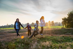 Family laughing and running on a hill at twilight