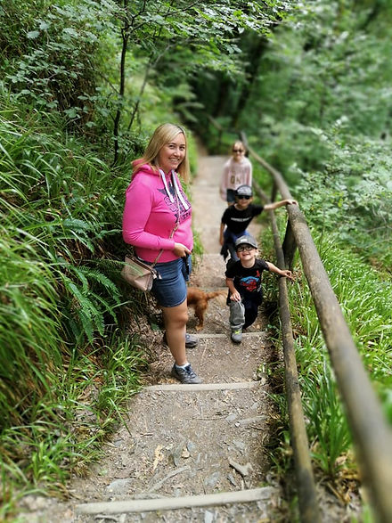 Lady holding dog lead and dog and children climbing steps, on a family walk