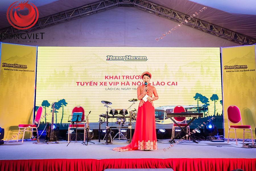 MC mặc trang phục áo dài với tông màu đỏ phù hợp với màu sắc chủ đạo của chương trình - Công ty sự kiện Rồng Việt