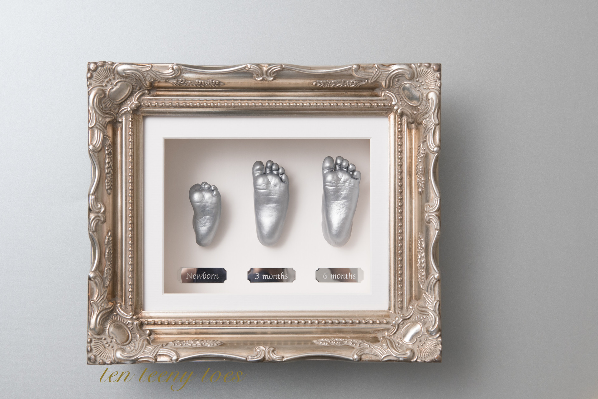 Three silver feet casts at newborn, three months and six months in a platinum vintage frame.