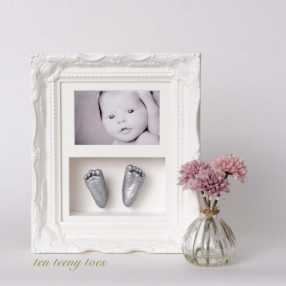 Two newborn feet casts with a photo in an ivory vintage frame.
