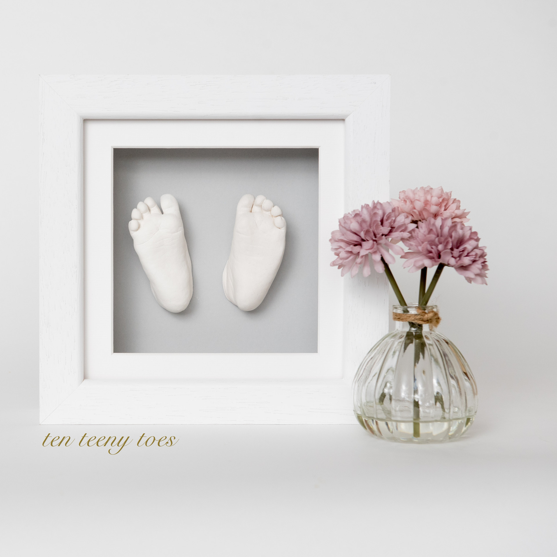 Ten teeny toes in a white contemporary hardwood frame.