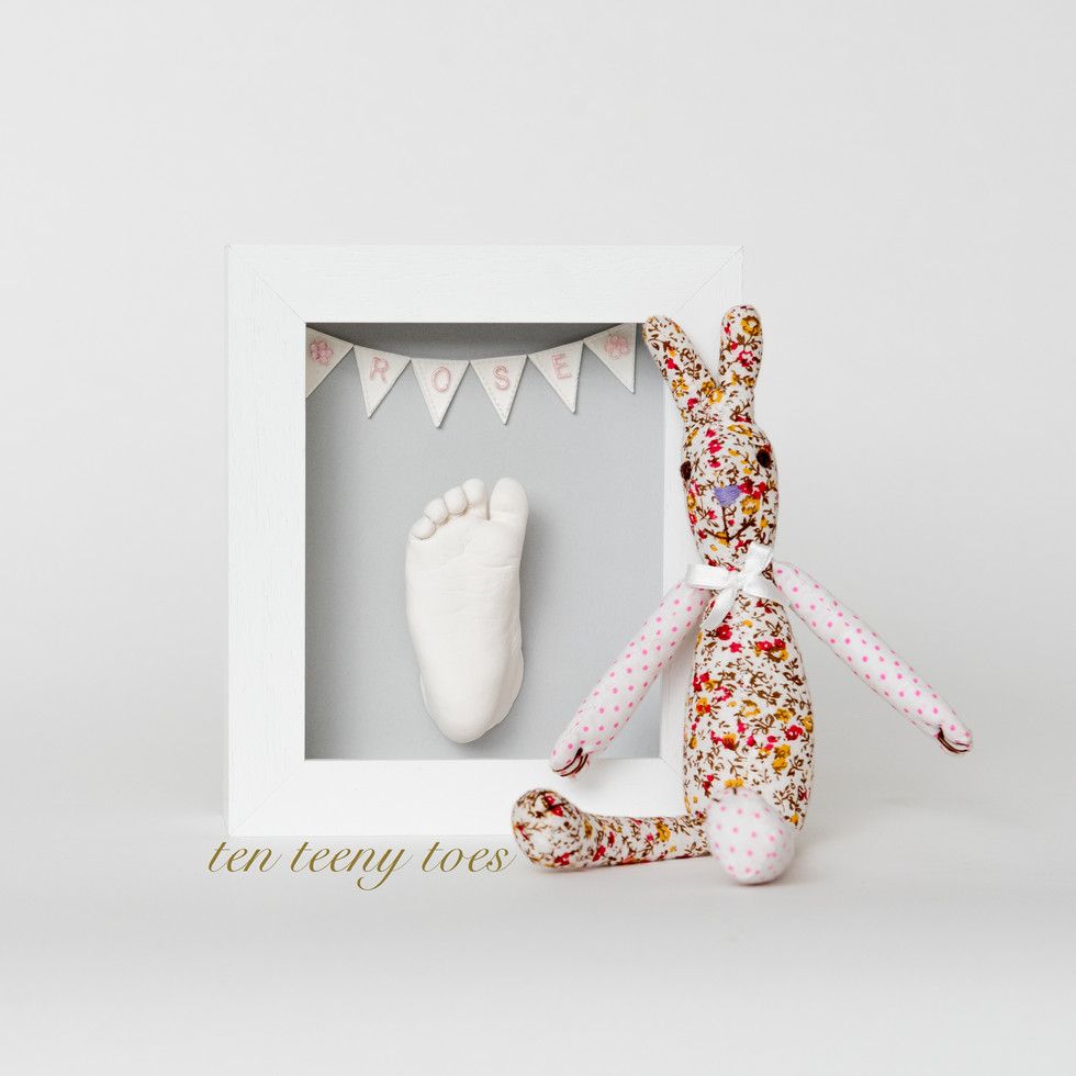 One white foot cast with personalised bunting in a contemporary white frame.