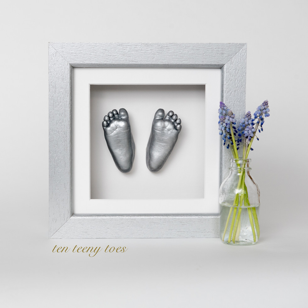 Ten teeny toes in a silver contemporary hardwood frame.
