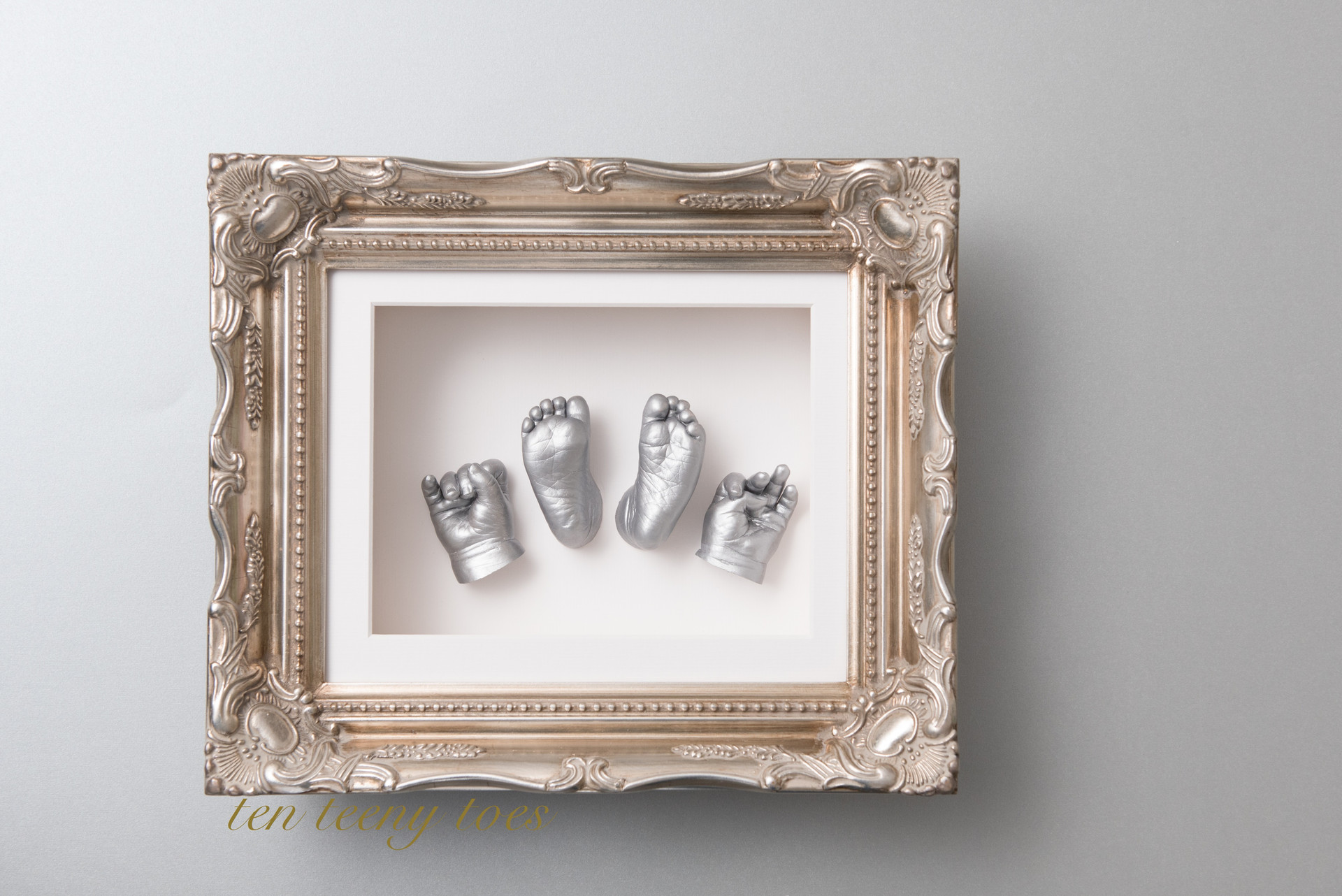Four newborn casts in a platinum vintage frame.
