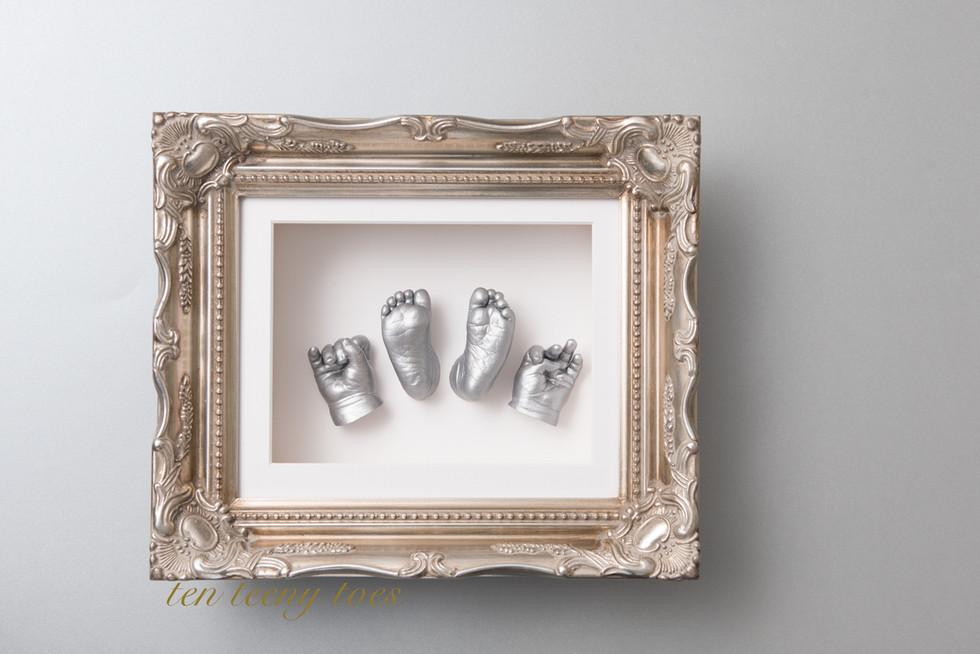 Four newborn casts in a platinum vintage frame.