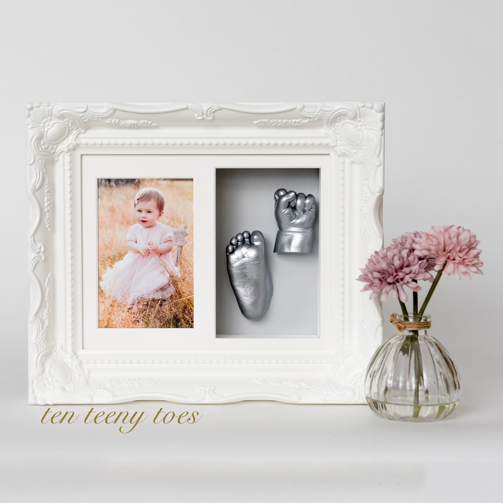 One hand and one foot cast with a photo in an ivory vintage frame.