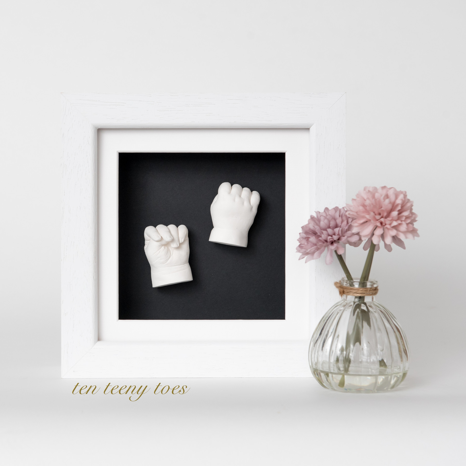 Two white hand casts in a white contemporary hardwood frame.