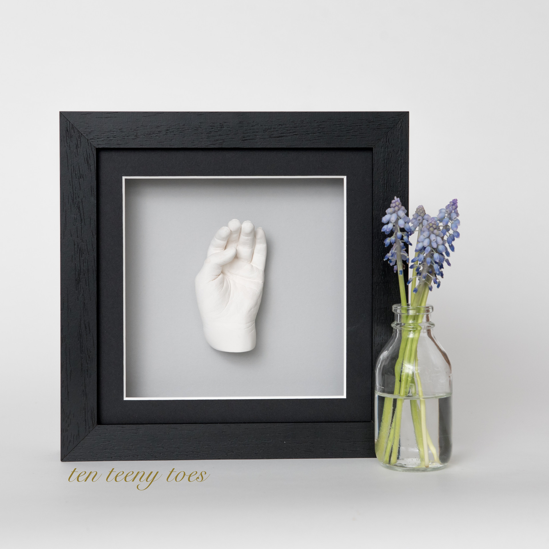 One two year old hand cast in a black contemporary frame.