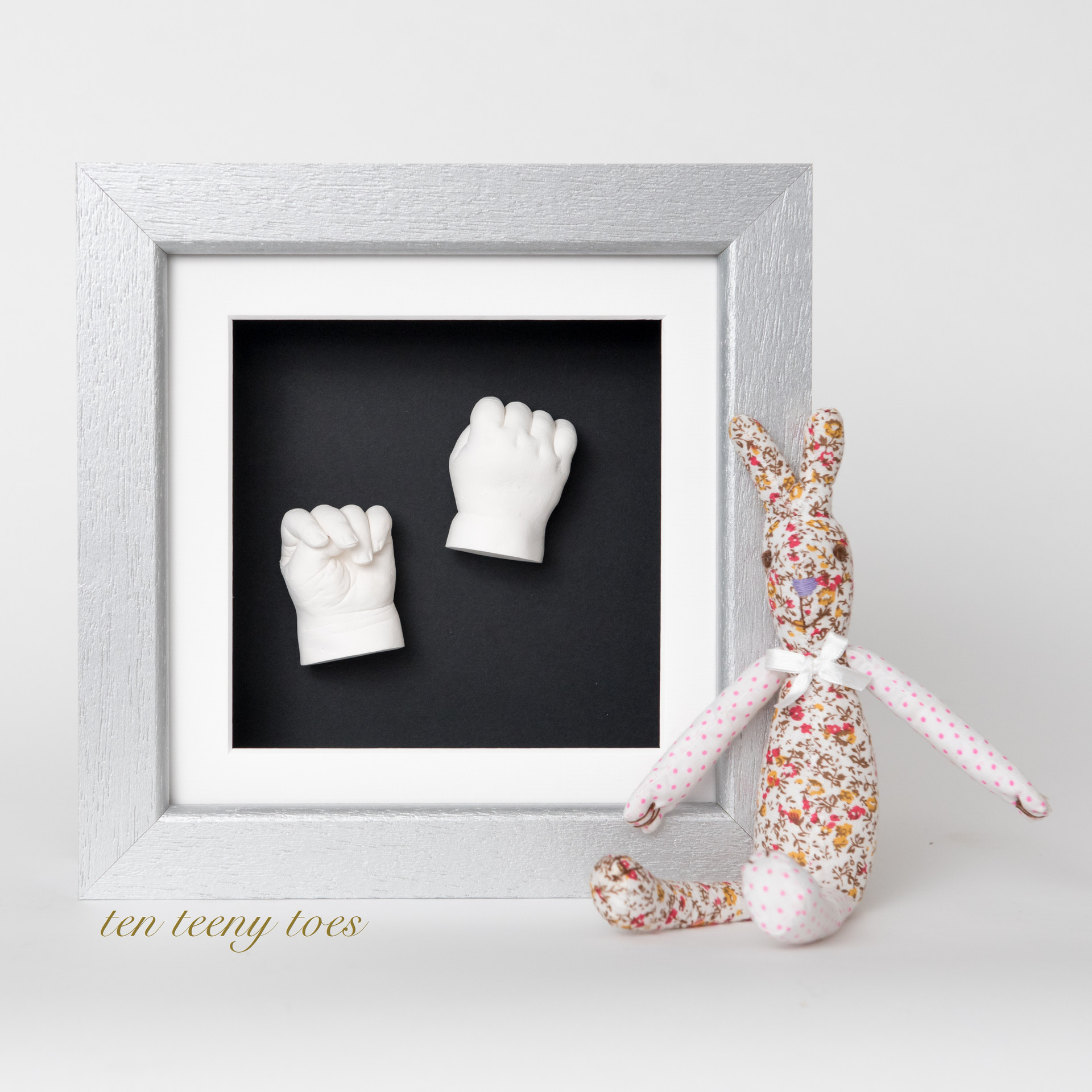 Two white hand casts in a silver contemporary hardwood frame.