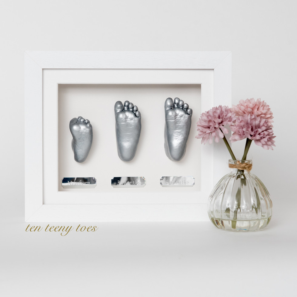 Three silver feet casts at newborn, three months and six months in a contemporary white hardwood frame.