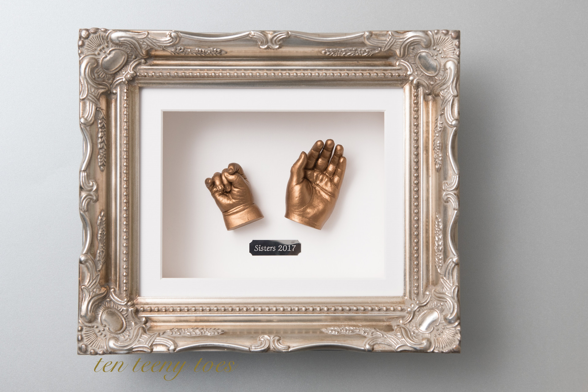 Two sibling hand casts in a platinum vintage frame with sisters name plate.