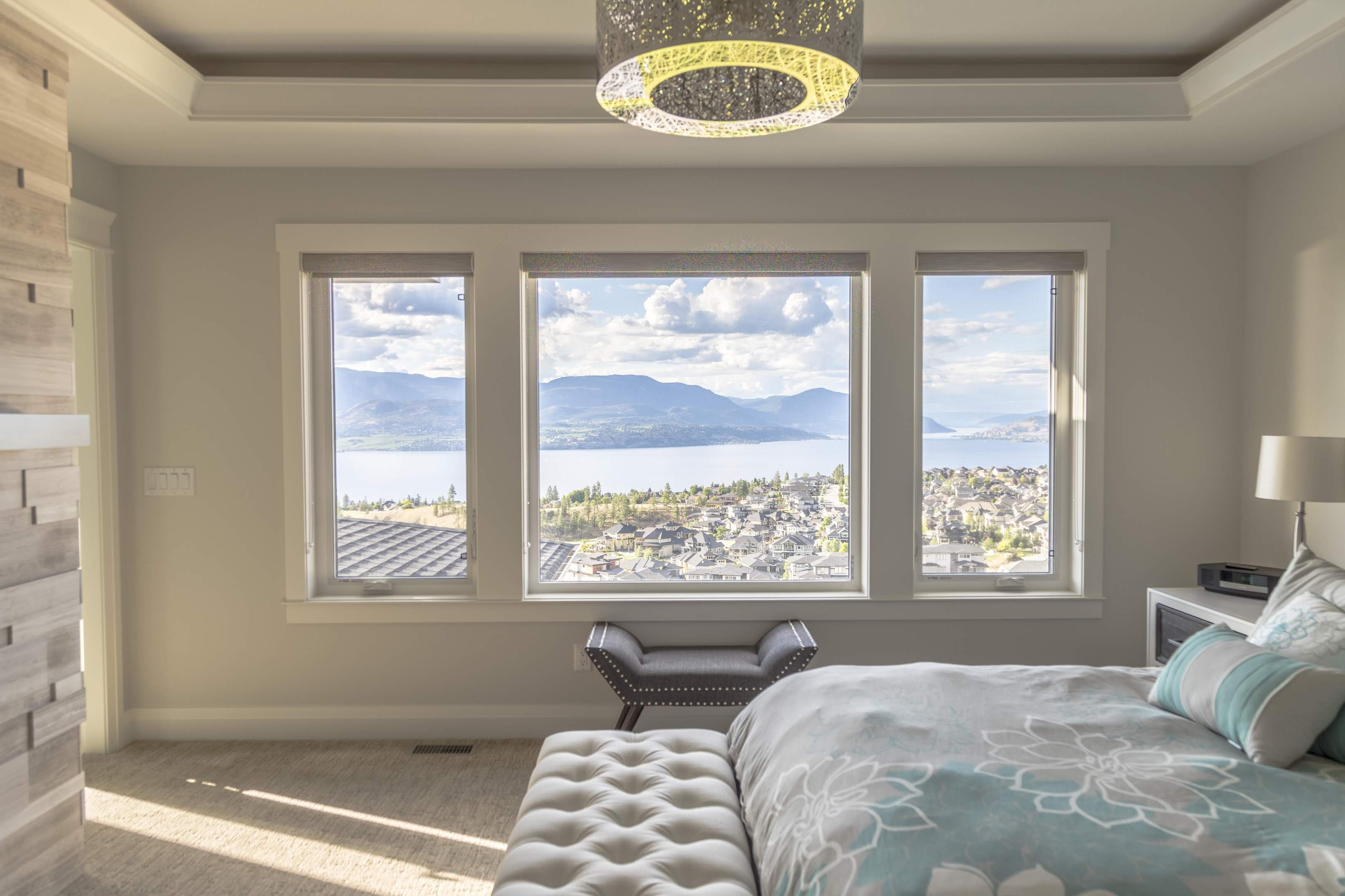 master bedroom with lake view and fireplace by impact builders