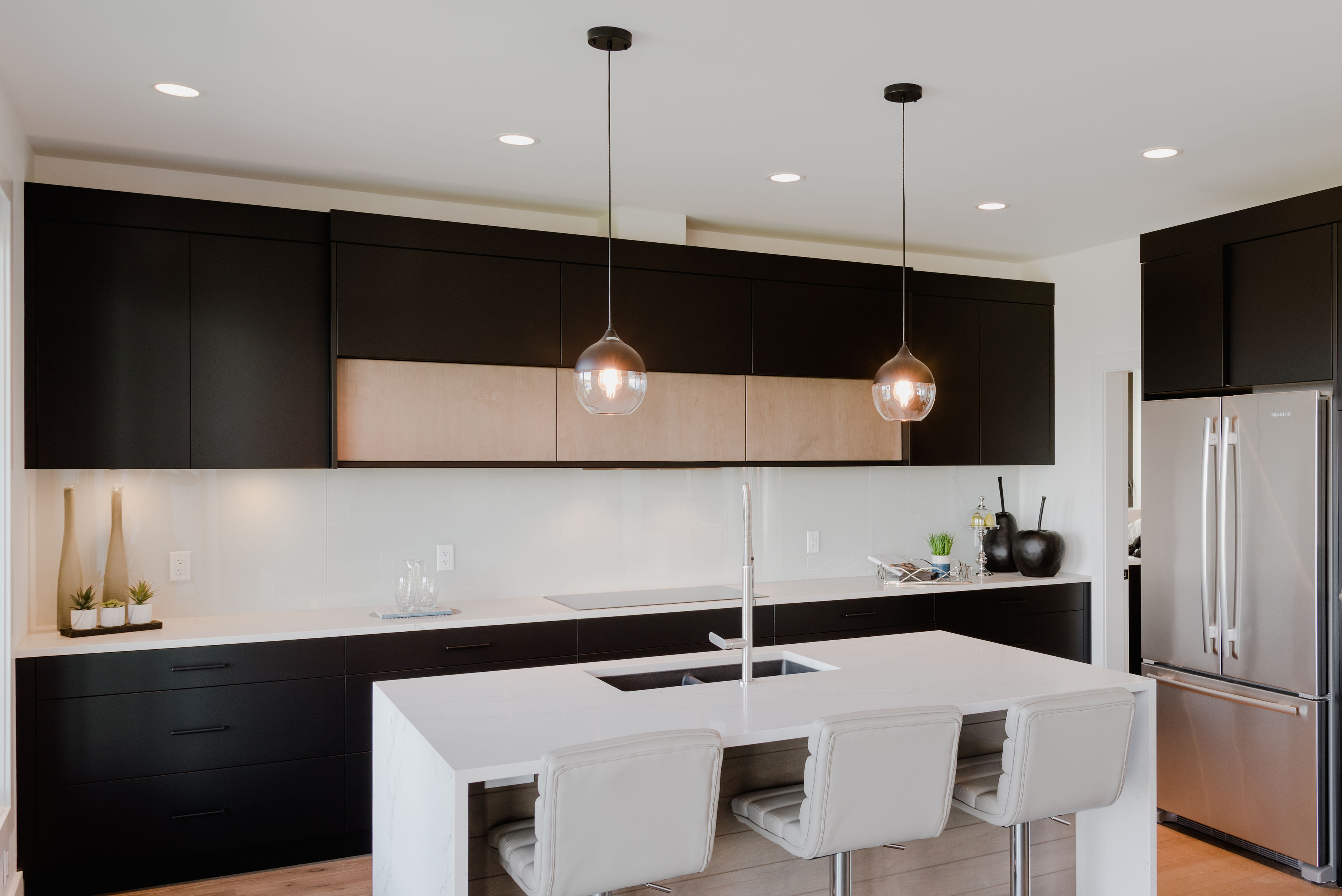 matte black kitchen with white island by impact builders