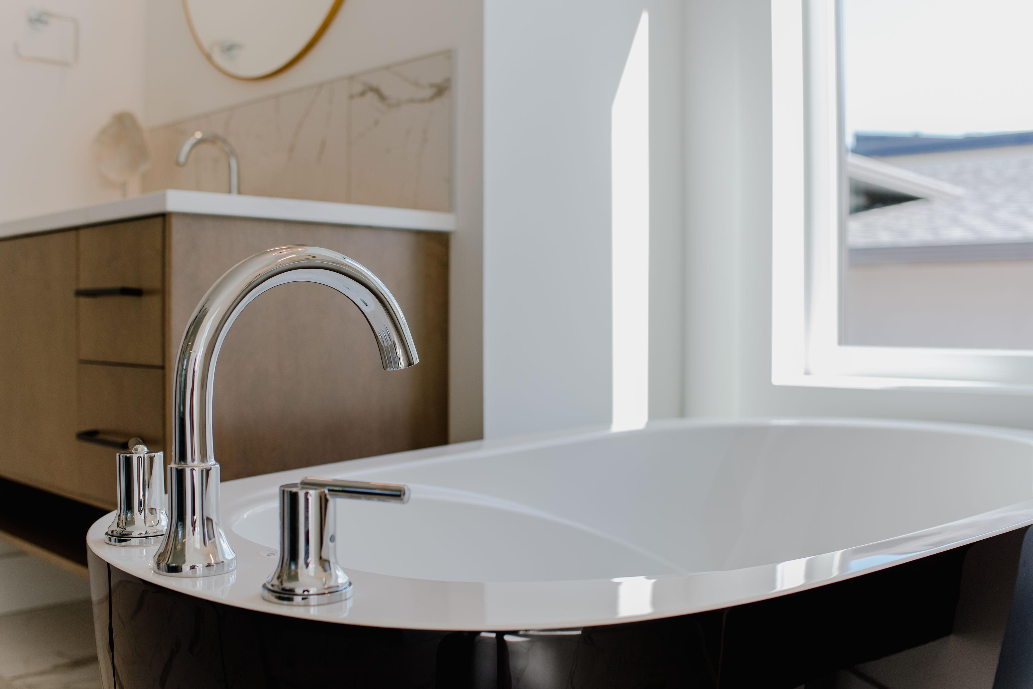 bathtub and wood vanity by impact builders