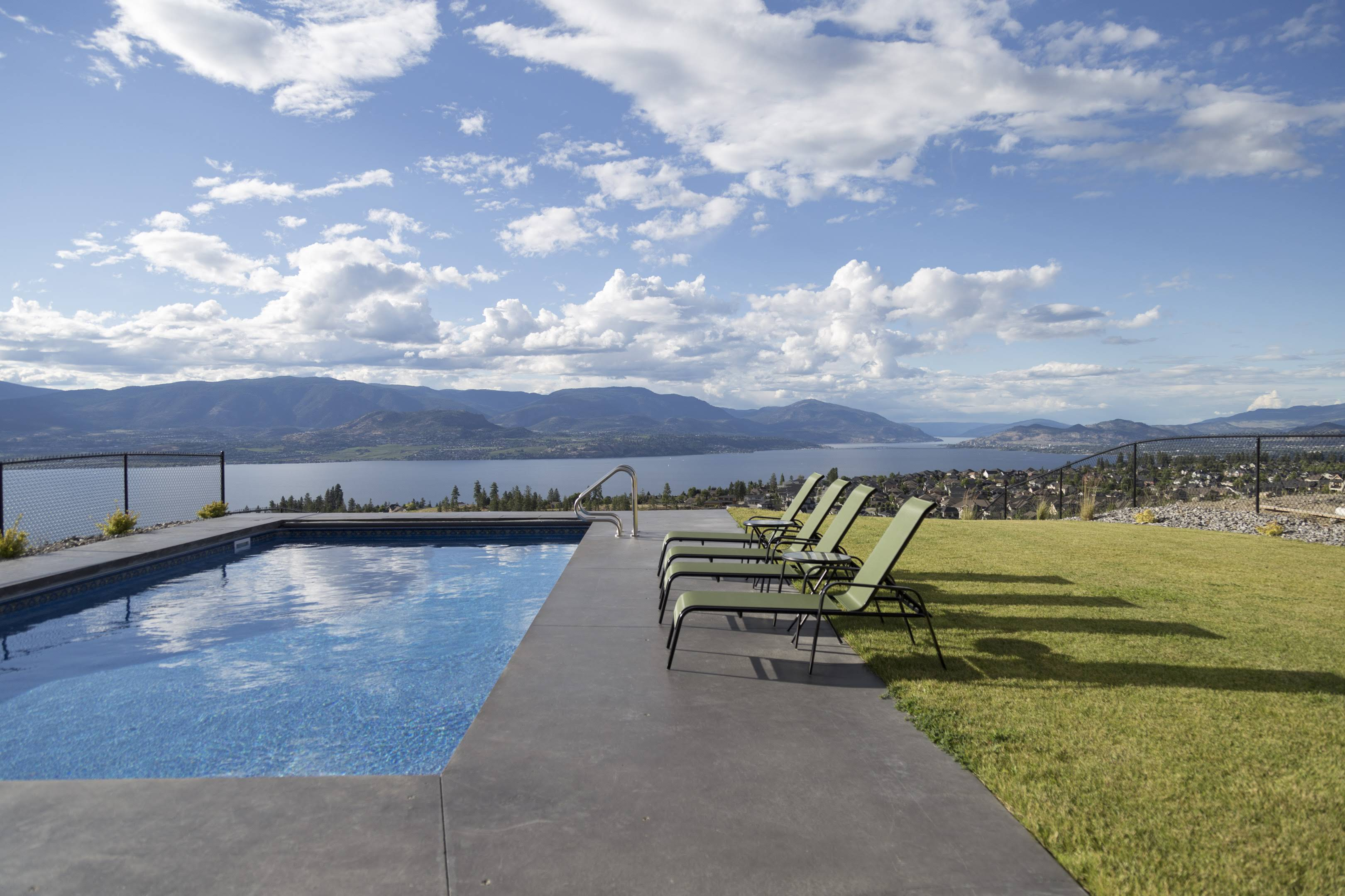 Swimming pool with lake view by Impact Builders