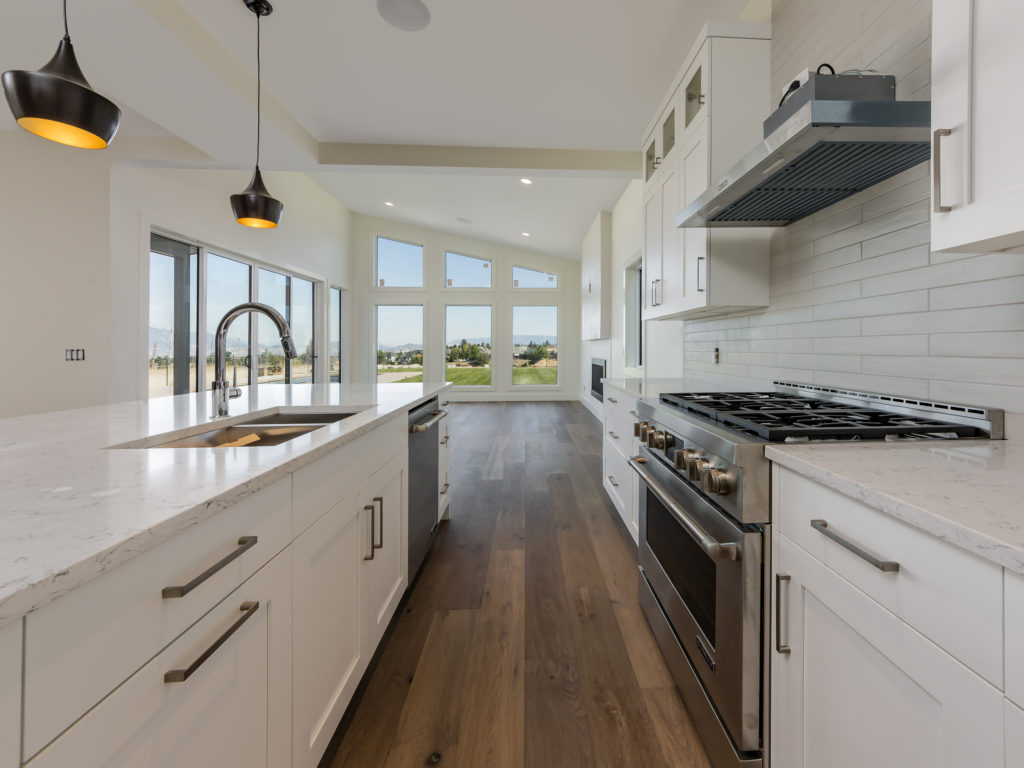 white Kitchen with island and lake view built by impact builders