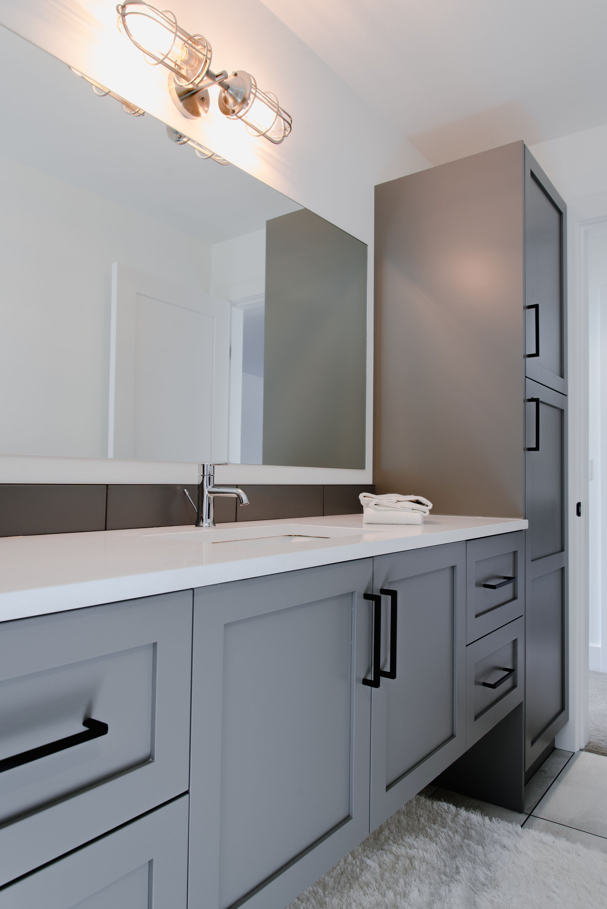 bathroom with grey cabinets by impact builders