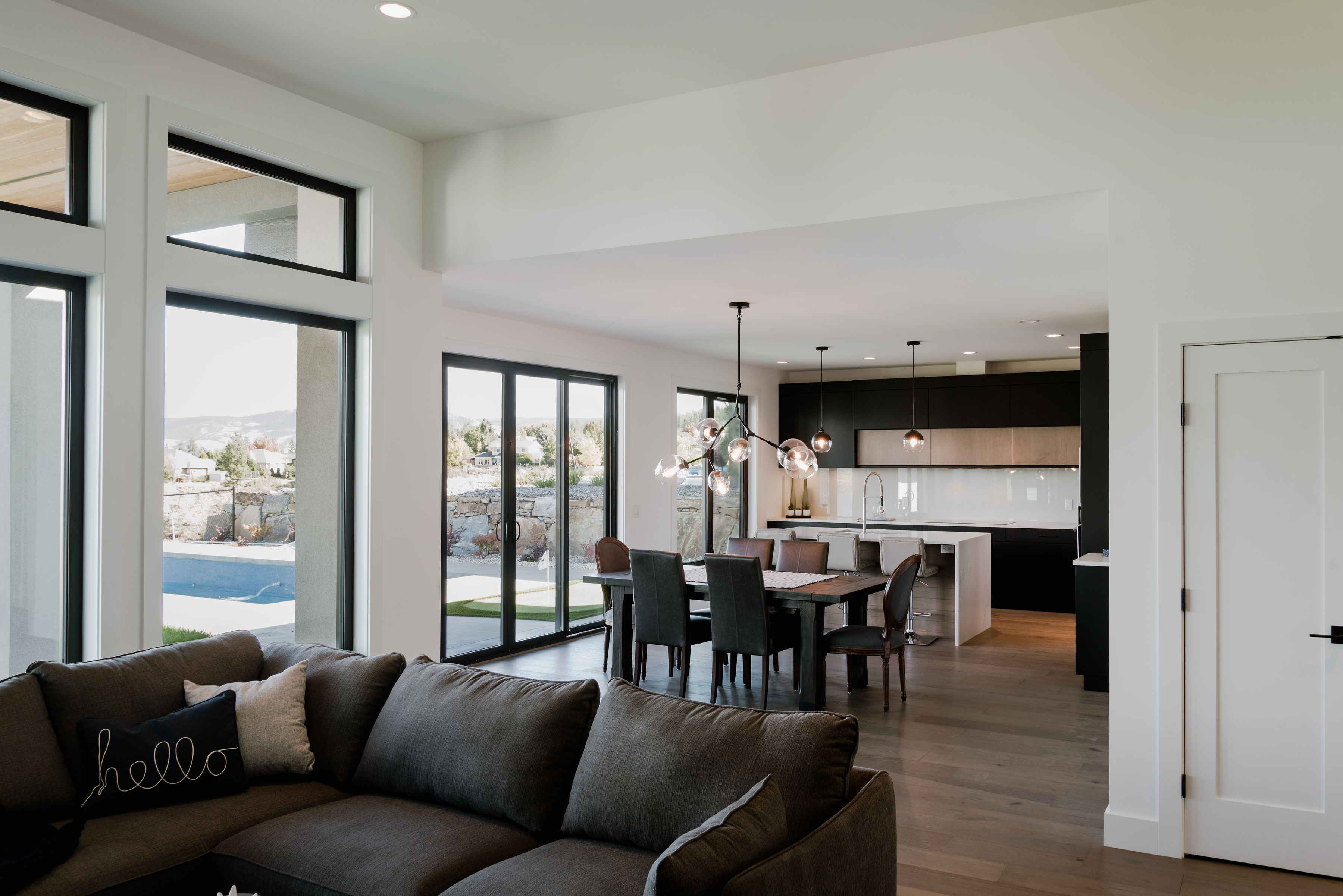 living room, dining room and matte black kitchen by impact builders