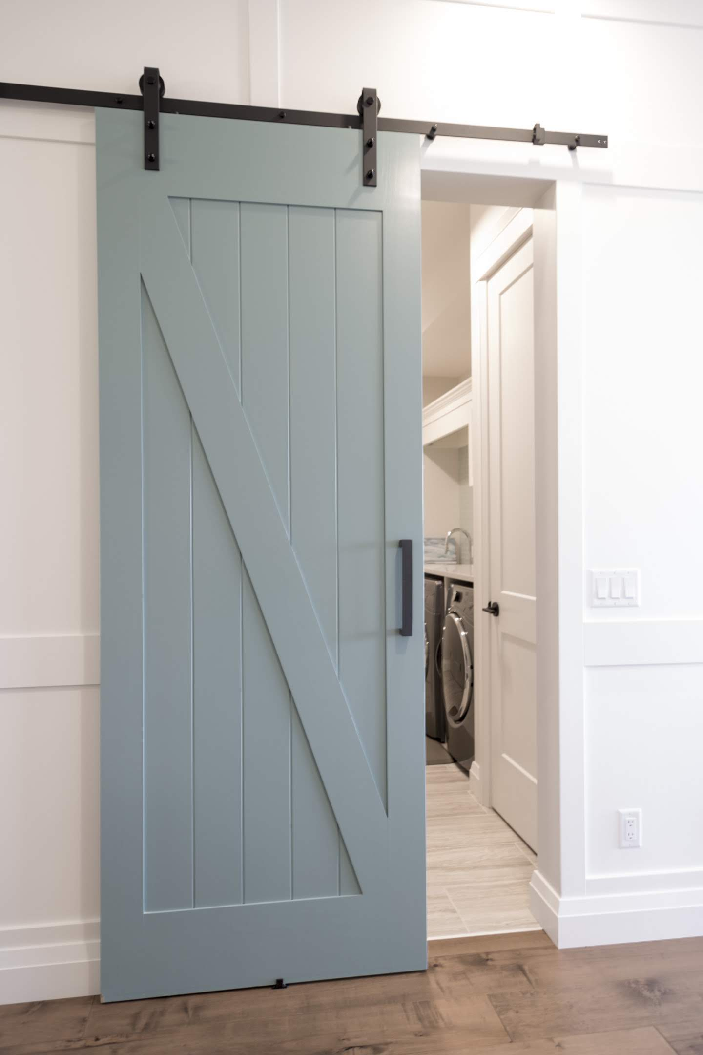 Blue barn door to laundry room built by impact builders