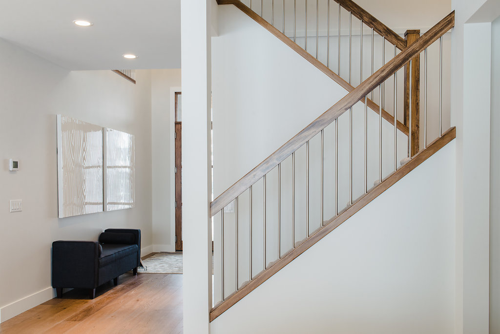 stairs with wooden railing by impact builders