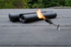 Heating and melting bitumen roofing felt