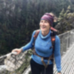 Aleks smiling at the camera in Nepal on a supension bridge