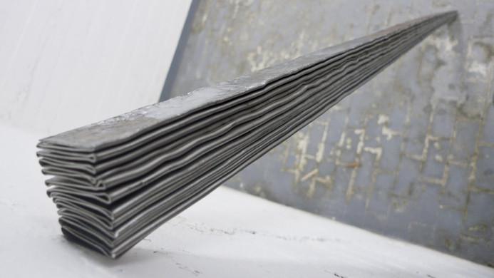 Plaque d'acier de format conventionnel pliée vingt-quatre fois à 90° avec plieuse manuelle, puis martelée à chaque opération pour achever la pliure.