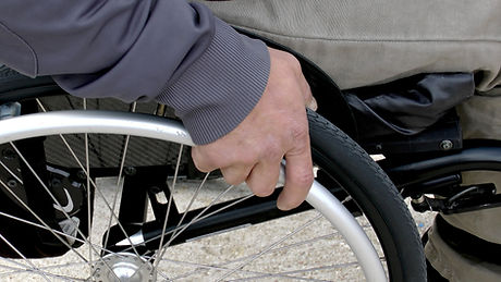 Picture of a hand holding onto the wheel of a wheelchair.