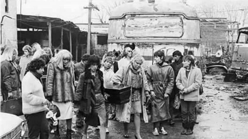 """Un grupo de chicas trans cargan el féretro de una """"Nancy de Villa Martelli"""", una compañera que murió atropellada en la autopista Panamericana, escapando de la policía. En el colectivo desvencijado de que se ve detrás vivían algunas de ellas. Publicada por Revista """"Esto!"""" de casos policiales en agosto de 1987 (Gentileza Archivo de la Memoria Trans)"""