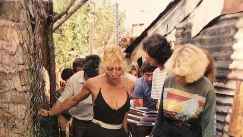 """Amigas de """"La Katy"""" transportan sus restos a través de un pasillo de Villa Madero (La Matanza), donde todas vivían. No alcanzó a cruzar la Autopista Richieri y murió embestida por el tráfico a mediados de los 80 (Gentileza Archivo de la Memoria Trans)."""