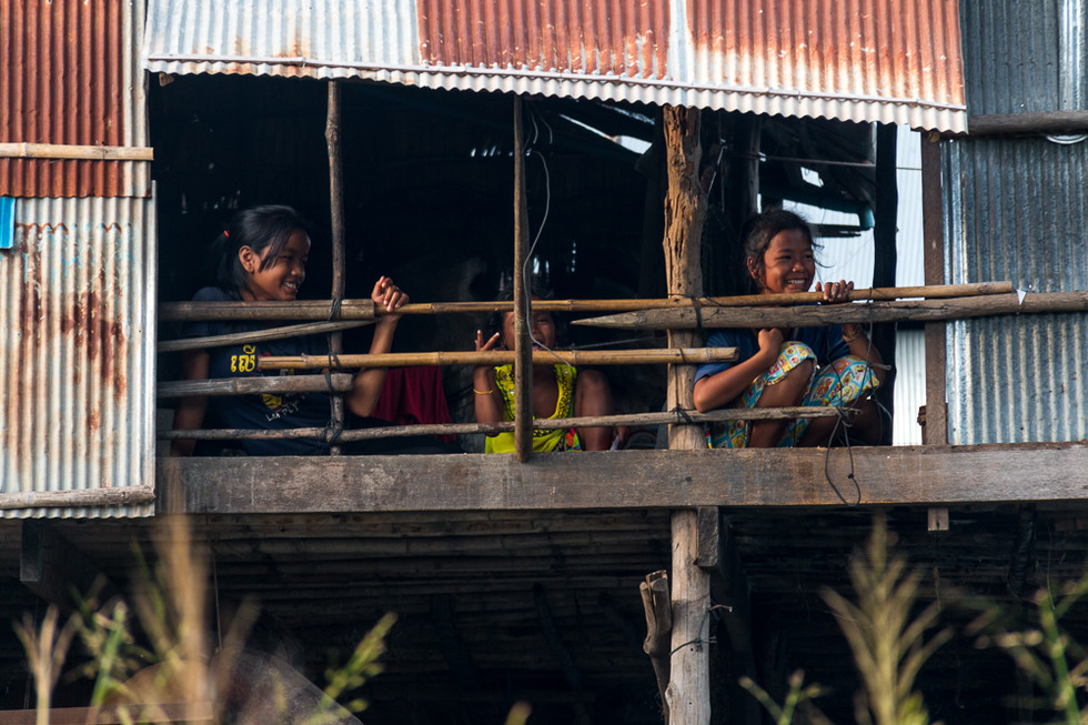 Kids smilling from their house in a floating village