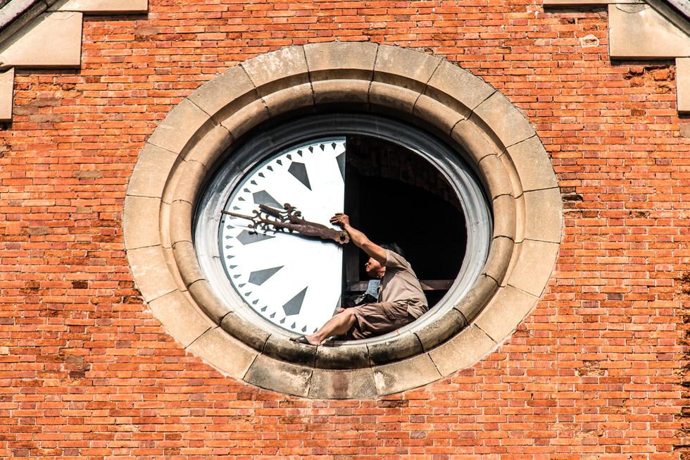 Men fixing a clock.