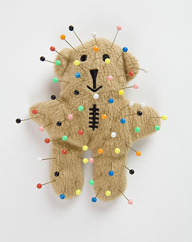 a quirky teddy bear like a voodoo doll i